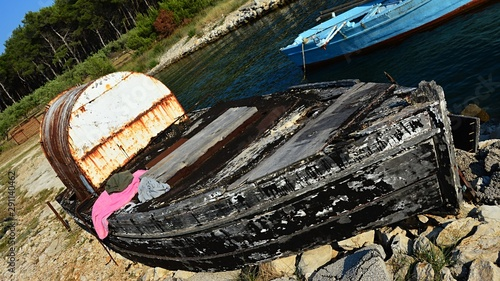 Cuadros en Lienzo Old decaying black fishing boat with white rusty booth used as a storage for fihsnets and other equipment, placed on rocky molo during hot summer day, blue fishing boat in background