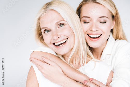 Obraz happy blonde mature mother and young daughter in total white clothes embracing isolated on grey - fototapety do salonu