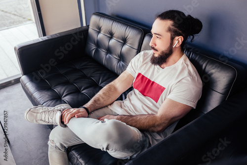 Handsome young man stylish hipster sitting on the sofa and looking aside Canvas-taulu