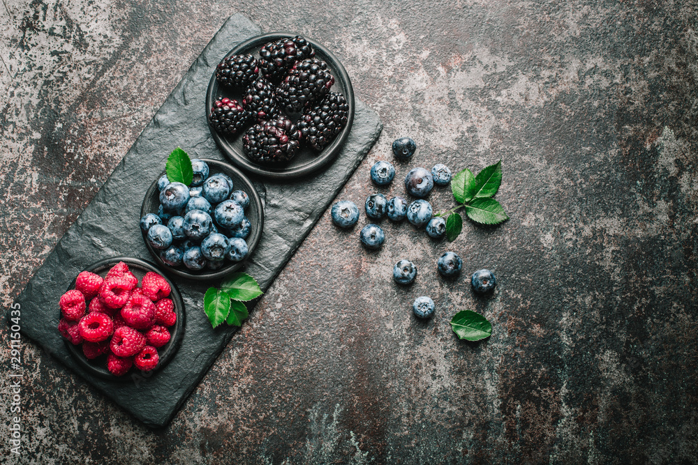Fototapety, obrazy: Fresh berries with raspberries, blueberries, blackberries in bowl on a stone stand on a dark metal background.