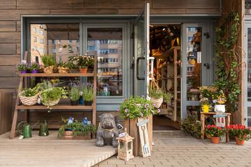 Ugodna cvjetna trgovina s policama s cvijećem i vrtnim ukrasima