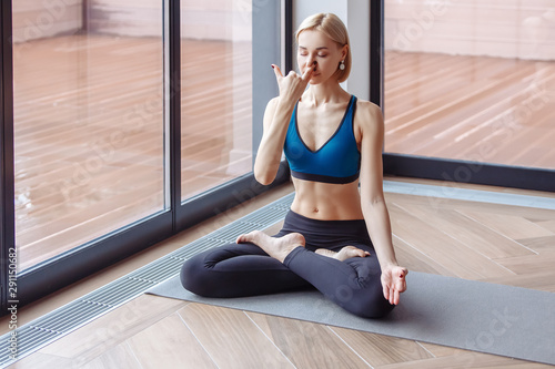 Deurstickers Ontspanning Charming slim woman yoga instructor doing padmasana basic yoga posture for pranayama in the spacious hall. The concept of breath control relaxation and meditation