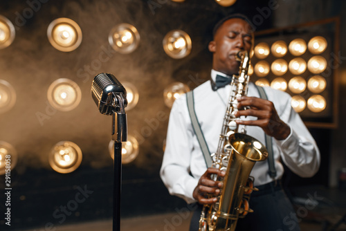 Photo  Male jazz performer plays the saxophone on stage