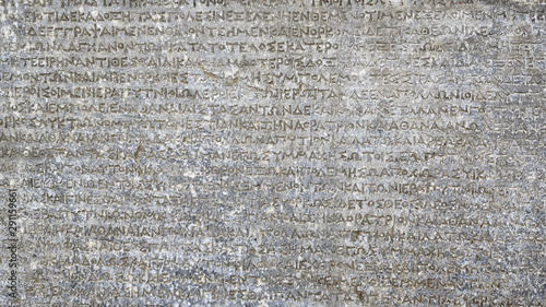 Naklejki historyczne ancient-greek-writing-on-rock-for-background-antique-inscription-carved-on-stone-old-script-text-close-up-gray-wall-with-historic-letters-vintage-texture-with-words-from-past-civilization