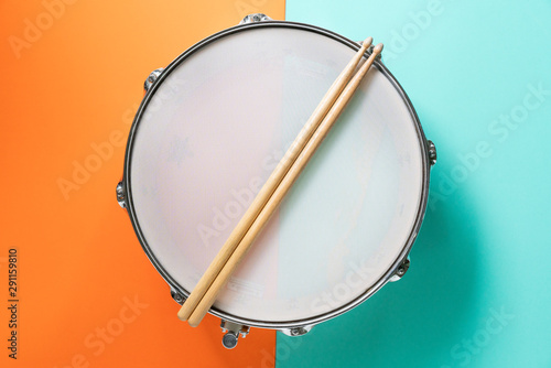 Drum stick on color table background, top view, music concept - 291159810