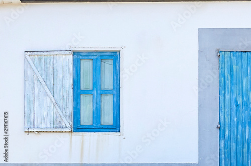 Fotografie, Obraz Blue door with a window closed in a mediterranean house with white wall
