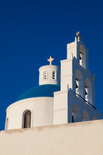 Dome And Bell Tower Of The Church Of Panagia Platsani Located In Oia City At Santorini Island In A Beautiful Early Spring Day
