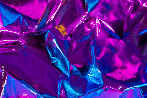 Crumpled blue-lilac background. Colored foil ?rumpled. Nonferrous metal. Blue-lilac silk fabric. Bright shiny background. Crumpled wrapping paper from a gift. - 291186685