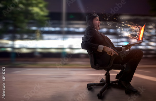 Mann fährt mit einen Börostuhl durch die Stadt mit Laptop in der Hand Canvas-taulu