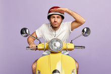 Serious Man Moped Driver Keeps Palm Near Forehead, Looks Into Distance, Notices Something On Road, Wears Protective Helmet And T Shirt, Poses On Yellow Motorbike, Isolated Over Purple Background