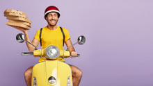 Pleased Man Delivers Fresh Pizza In Carton Boxes, Transports Dish From Restaurant Where He Works As Courier, Wears Helmet, Uses Own Transport, Isolated Over Purple Background, Has Glad Expression