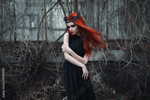 Carta da parati A fragile sad goth girl with red hair in a crown and a black dress stands in the