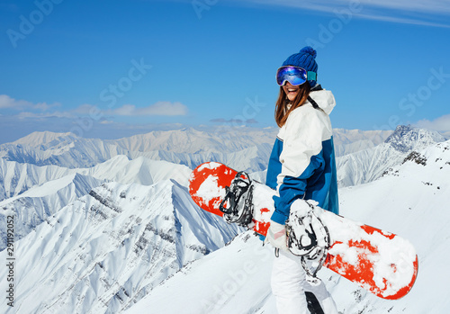 Obrazy Snowboard   cheerful-girl-snowboarder-on-the-background-of-peaks-snowy-mountains