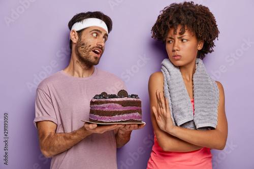 Fotografija  Dissatisfied Afro American woman makes refusal gesture, asks not suggest eating