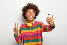 Photo Of Carefree Curly Haired Young Woman Takes Selfie Portrait On Mobile Phone, Shows Peace Gesture, Wears Striped Colorful Jumper, Headphones Around Neck, Uses Technology During Leisure Time