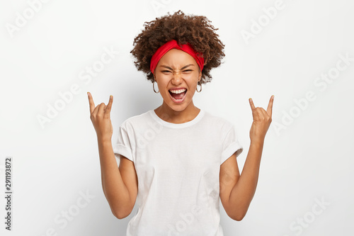 Fototapeta  Photo of energetic young African American woman makes rock n roll gesture, enjoys cool music, smirks face, dressed in casual wear, poses against white background
