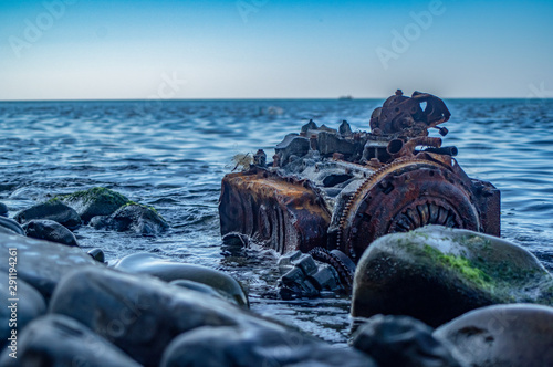 Old rusty engine lying among stones in the water. Canvas-taulu