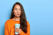Leinwandbild Motiv Photo of pensive brunette woman purses lips, looks thoughtfully aside, holds takeout coffee, makes decision in mind, plans her day, wears orange jumper, stands over blue wall. Asian girl with beverage