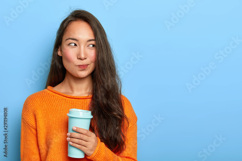 Obraz na plátne  Photo of pensive brunette woman purses lips, looks thoughtfully aside, holds takeout coffee, makes decision in mind, plans her day, wears orange jumper, stands over blue wall