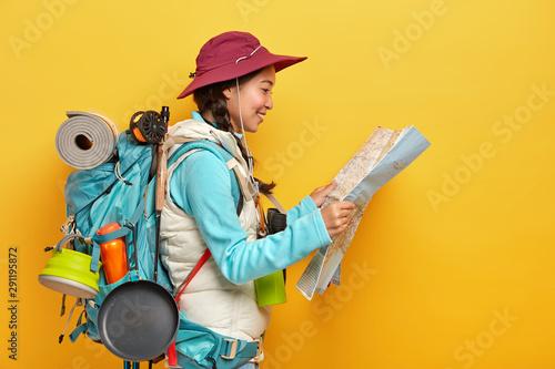 Stampa su Tela  Sideways shot of Asian female tourist studies map, finds new destination to expl