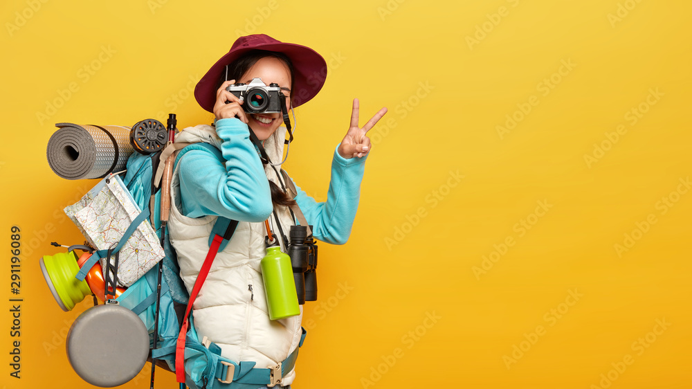 Fototapeta Photo of active female model makes shots on retro camera, shows peace gesture, dressed in casual clothes, carries rucksack, thermos and binoculars, has journey in wild place, isolated on yellow