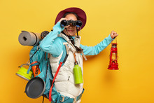Horizontal Shot Of Curious Female Backpacker Explores Tourist Destination, Uses Binoculars, Dressed In Active Wear, Holds Kerosene Lamp Carries Travelling Items With Rucksack Isolated Over Yellow Wall