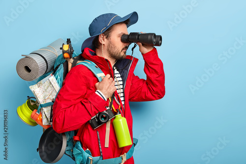 Canvas Print Photo of male explorer dressed in casual wear, keeps binoculars near eyes, wears hat and jacket, hikes in mountains, isolated over blue background copy space area for your advertisement