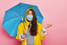 Photo Of Serious Brunette Woman Raises Palm, Wears Medical Mask For Protecting Herself From Virus And Catching Disease, Stands Under Umbrella Against Pink Background. Autumn And Sickness Concept