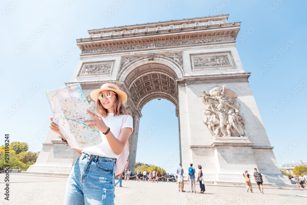 Fototapeta Happy Asian tourist girl enjoys the view of the majestic and famous Arc de Triomphe or Triumphal arch. Solo Travel and voyage to Paris and France