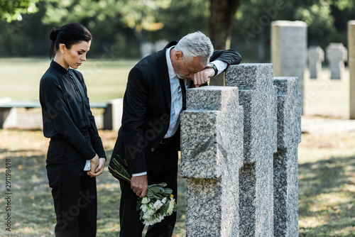Photo attractive woman holding flowers near tombstones and sad man