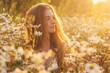 Side portrait of pretty blond woman sitting in chamomile field