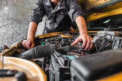 Obraz na plátně  Car service worker repairing vehicle
