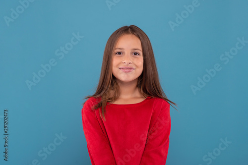 Half length portrait of a smiling young girl wearing red shirt against  blue background with copy space in studio Canvas-taulu