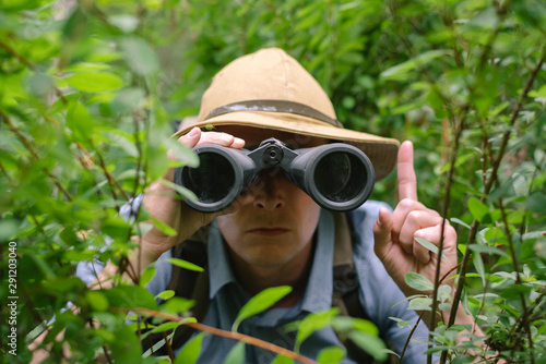 Carta da parati Tourist looking through binoculars, hiding in trees and showing his finger up