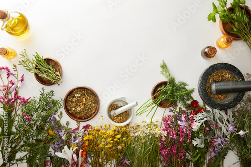 top view of mortars and pestles with herbal blends near flowers on white backgro Wallpaper Mural