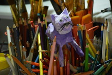 Paper Mache Cat Amidst Art Supplies
