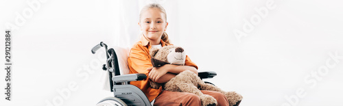 Carta da parati  panoramic shot of smiling kid holding teddy bear and sitting on wheelchair