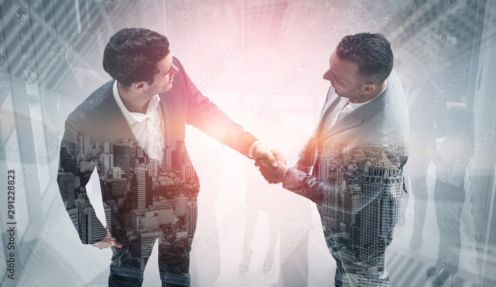 Fototapeta Double exposure image of business people handshake on city office building in background showing partnership success of business deal. Concept of corporate teamwork, trust partner and work agreement.