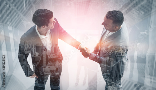 Fotomural  Double exposure image of business people handshake on city office building in background showing partnership success of business deal
