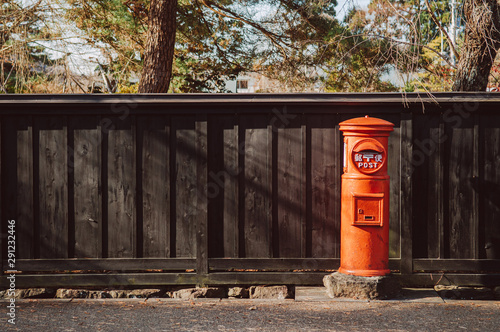 Fotografie, Obraz  Red vintgae Japanese mail letter postbox and black wooden wall