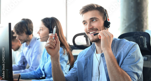 Obraz Portrait of call center worker accompanied by his team. Smiling customer support operator at work. - fototapety do salonu