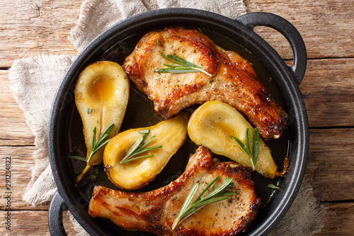 Obraz Holiday recipe for baked pork chops with pears and rosemary in honey sauce served in a pan close-up. Horizontal top view - fototapety do salonu