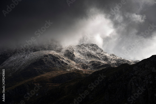 Foto auf AluDibond Schwarz Stunning moody dramatic Winter landscape image of snowcapped Tryfan mountain in Snowdonia with stormy weather brooding overhead