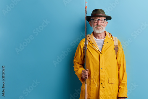 Poster Peche bearded old man in glasses going fishing, close up photo. isolated blue background, studio shot. copy space hobby, interest