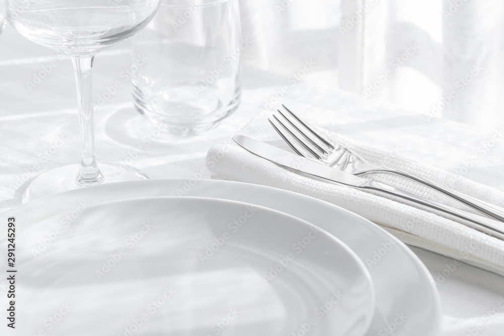 Fototapety, obrazy: Table setting white and grey colour. Empty glasses and plates set with napkin and cutlery on white table cloth. Restaurant interior background.