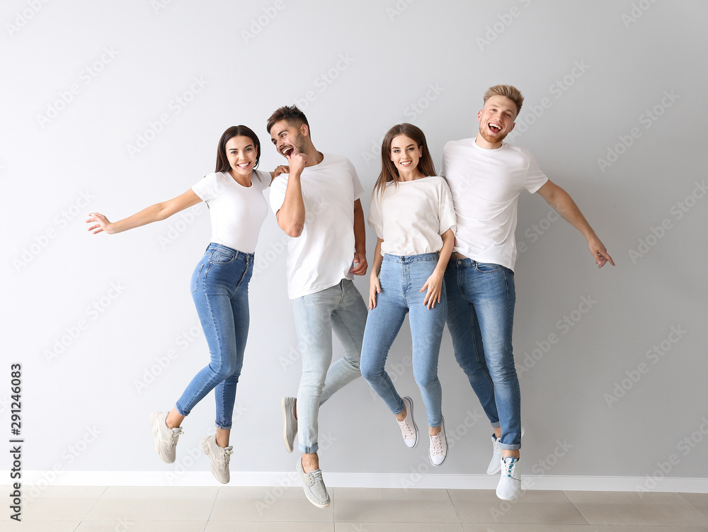 Fototapeta Group of jumping young people in stylish casual clothes near light wall