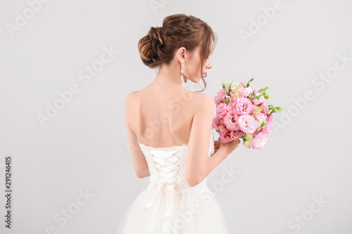 Fotomural Beautiful young bride with wedding bouquet on light background, back view