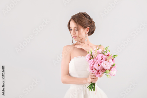 Portrait of beautiful young bride with wedding bouquet on light background Wallpaper Mural