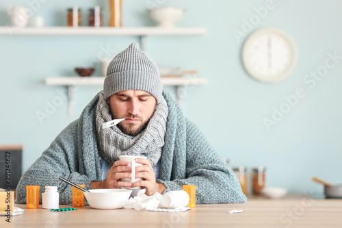 Photo Sick man sitting at kitchen table