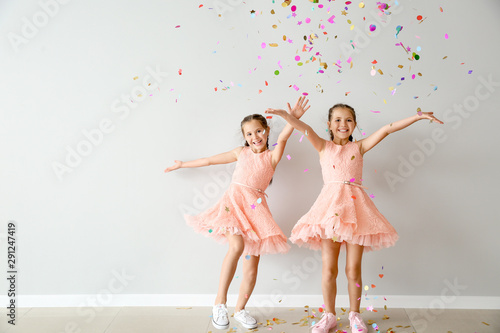 Fotomural  Portrait of happy twin girls with falling confetti near light wall